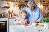 Kid And Grandmother Are Cooking Italian Pizza In Cozy Home Kitchen For Family Dinner. Cute Girl Is H poster