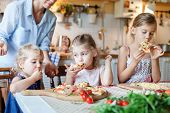Children Are Eating And Tasting Italian Homemade Pizza Cooking Themselves Together. Cute Kids Are En poster