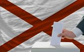 pic of alabama  - man putting ballot in a box during elections in front of flag american state of alabama - JPG