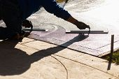 Construction Worker Smoothing Wet Cement With Trowel Tools poster