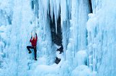 Man in Red Coat climbing ice