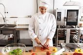 Photo of satisfied woman chef wearing white uniform cooking meal with fresh vegetables in kitchen at poster