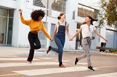 Three millennial hip girlfriends holding hands and laughing as they run across a pedestrian crossing poster