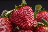Ripe Strawberries On A Black Background. A Close Up Photo Of Ripe Red Strawberries. poster
