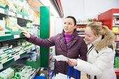 Two woman choosing bio food produces in dairy supermarket with shopping list
