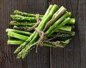 Bunches of asparagus tied with twine on a wood background. Overhead view in horizontal format.