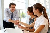 Salesman shaking hands to clients