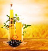 Foto de aceite de oliva naturaleza muerta en mesa de madera sobre la puesta de sol, tarro de cristal con aceite y aceitunas frescas verduras