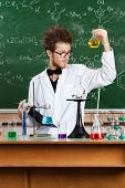 Mad professor examines Bunsen flask with yellow water after the experiment in his laboratory