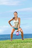 picture of snatch  - fitness exercise woman lifting kettlebell during strength training exercising outdoors on grass by the ocean - JPG