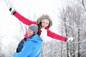 Winter fun couple playful together during winter holidays vacation outside in snow forest. Happy you