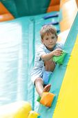 young happy boy having fun on trampoline outdoors