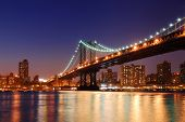New York City Manhattan Bridge sobre o Rio Hudson com horizonte depois da noite do sol Ver os iluminados wi