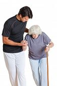 Young trainer assisting senior woman holding walking stick over white background