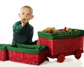 An adorable preschooler blowing a toy trumpet by a red wicker