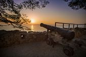Old rusty cannon at sunset