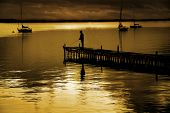 picture of dock a pond  - Dock floating in lake with sky and fisherman - JPG