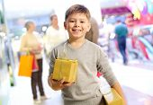 Portrait of happy child holding gift box with his family on background