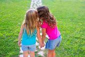 friends sister girls whispering secret in ear in grass garden track park outdoor