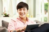 Young Chinese Man Using Digital Tablet Whilst Relaxing On Sofa At Home