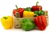 red,yellow and green bell peppers (capsicum) in a wooden crate on a white background