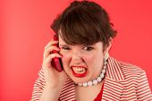 Young woman is having an angry phone call at the smartphone