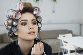 Closeup of a female model in hair curlers applying lip gloss