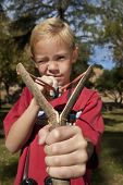 Closeup portrait of a blond boy using slingshot