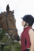 stock photo of riding-crop  - Side view of a young woman in riding hat with a horse outdoors - JPG