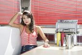 Portrait of a beautiful young woman waiting at the diner table