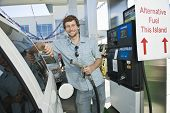 Portrait of smiling man refueling cropped car at natural gas station