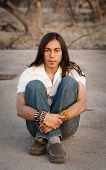 image of native american ethnicity  - Handsome young man with long hair in an outdoor setting - JPG