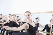 pic of ballet barre  - Row of female ballet dancers practicing at barre in rehearsal room - JPG