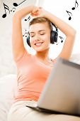 foto of track home  - happy woman with headphones and laptop at home - JPG