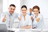 business concept - business team showing thumbs up in office