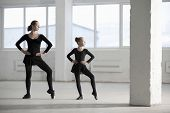 Full length of ballerina teaching young girl in empty warehouse