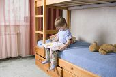 stock photo of bunk-bed  - Full length of young boy reading book on bunk bed - JPG