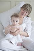 Smiling mother sitting with baby boy in bedroom