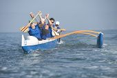 Multiethnic outrigger canoeing team in race