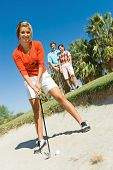 Low angle view of a female golfer hitting ball from sand trap with friends in background