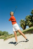 Low angle view of a female golfer hitting ball from sand trap against clear blue sky
