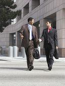 Dos hombres de negocios multiétnica caminando en la calle contra edificios de la ciudad