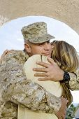 stock photo of military personnel  - Young soldier embracing his woman outdoors - JPG