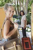Dos turistas mujeres multiétnicos felices con equipaje