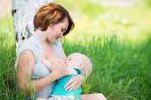 stock photo of eat grass  - Young mother breastfeeding a baby in nature - JPG