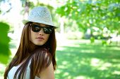 young beautiful lady outdoor portrait, girl in summer park  in sunglasses and fedora with long brown