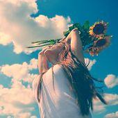joven mujer hermosa disfrutando el verano, la juventud y la libertad, sosteniendo los girasoles por encima de la cabeza, contra blu