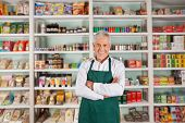 Portrait of happy senior male owner standing arms crossed against shelves in supermarket