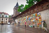 CRACOW, POLAND - JUNE 28: Outdoor gallery on the city walls of Krakow on 28 June 2013. This famous street gallery is located on the city walls at St. Florian Gate, the focal point of Krakow old town.