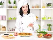 Beautiful girl chief-cooker with pizza on kitchen background